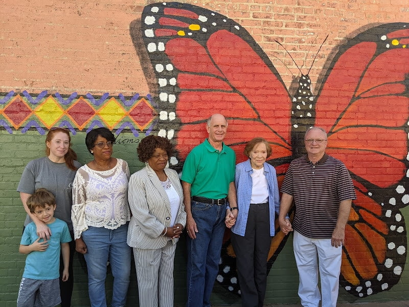 Group standing in front of wall mural at Cafe Campesino